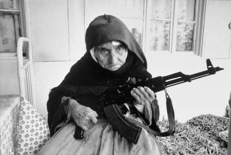 A 106-year-old woman sits in front of her home guarding it with a rifle, in Degh village, near the city of Goris in southern Armenia. (Image Credit: Armineh Johannes / UN Photo)