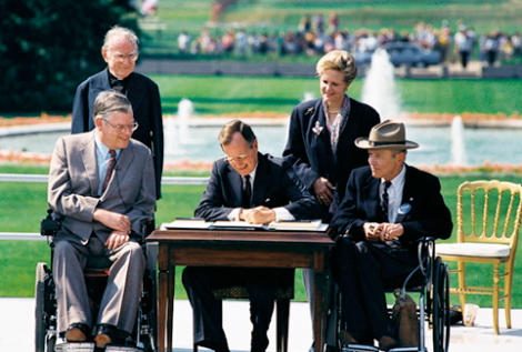President George H. W. Bush signs the Americans with Disabilities Act of 1990 into law. (Image Credit: WikiMedia Commons)